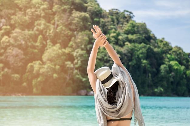 Asiatin, die auf ferien auf einer insel sich entspannt und nach dem perfekten berg sucht