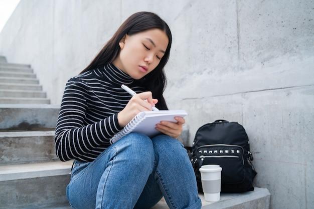 Asiatin, die auf notizbuch schreibt.
