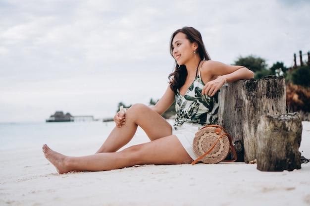 Asiatin, die auf weißem sand durch den indischen ozean sitzt