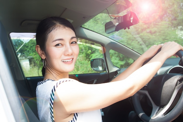 Asiatin, die auto, sonnigen tag fährt. uv-schutz oder hautpflegekonzept