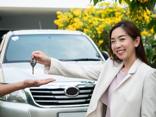 Asiatin, die autoschlüssel zu einem mann hält. autofahren, reisen, fahrzeugmiete, sicherheitsversicherung