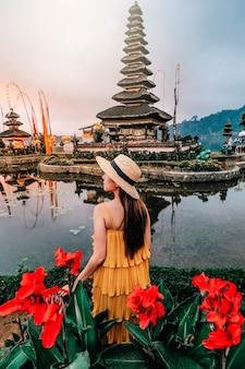 Asiatin, die bei pura ulun danu beratan den sich hin- und herbewegenden tempel in bali, indonesien am morgen reist.