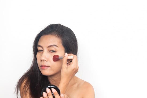 Asiatin, die bürste auf backen anwendet. make up und beauty. anti aging und chirurgie.