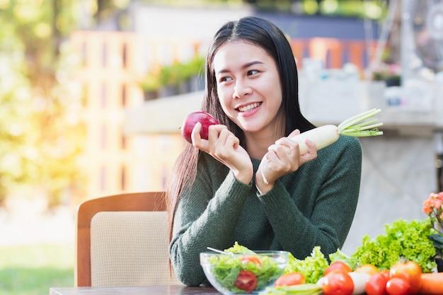 Asiatin, die das gemüse und frucht aufwerfen mit glücklichem hält.
