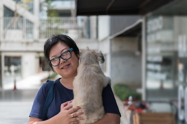 Asiatin, die den hund so süß an der kaffeestube umarmt