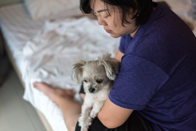 Asiatin, die den hund so süß auf bett im schlafzimmer umarmt