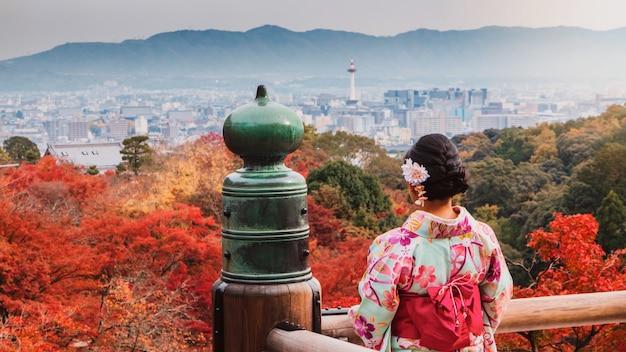 Asiatin, die den schönen gehenden kimono und die reise im japanischen garten innerhalb des tempels mit rotahornblättern im herbst trägt.