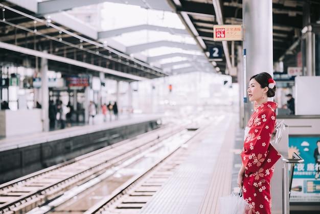 Asiatin, die den traditionellen japanischen kimono wartet auf einen zug auf einer stationsplattform trägt