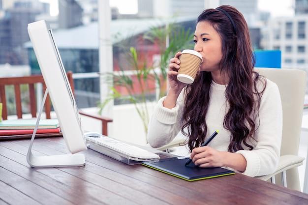 Asiatin, die digitales brett beim betrachten des computermonitors im büro trinkt und verwendet