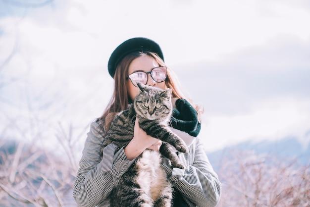 Asiatin, die draußen eine katze in japan-winter hält