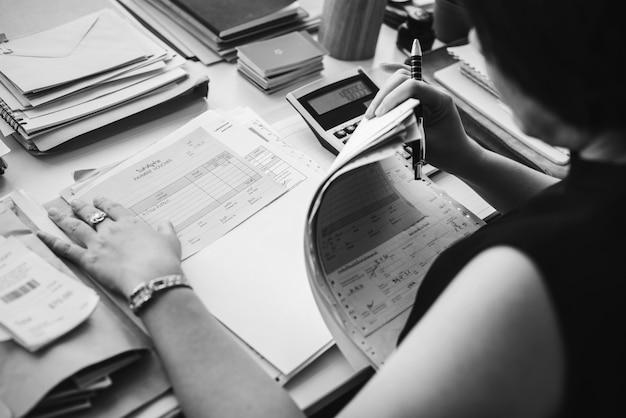 Asiatin, die durch schreibarbeit arbeitet