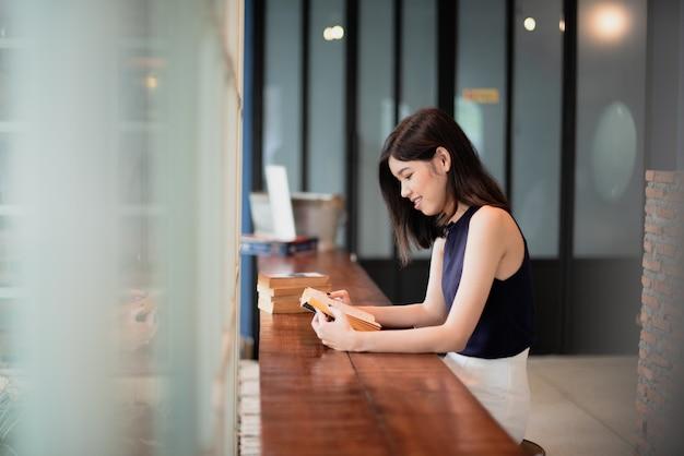Asiatin, die ein buch am coffeeshop liest.