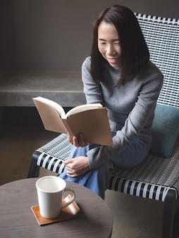 Asiatin, die ein buch auf dem stuhl liest