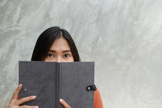 Asiatin, die ein buch auf einem grauen hintergrund liest.
