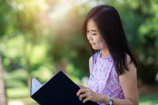 Asiatin, die ein buch im park mit grünem naturhintergrund liest