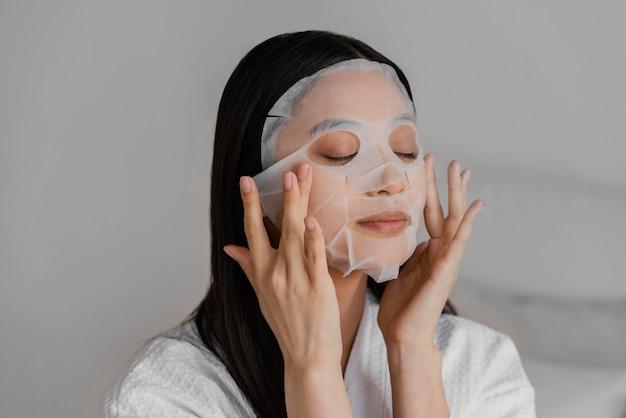 Asiatin, die eine blattmaske benutzt