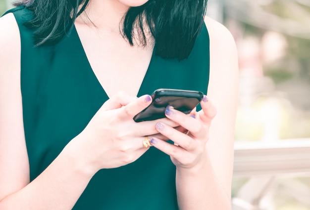 Asiatin, die eine simsende mitteilung des intelligenten telefons steht und verwendet