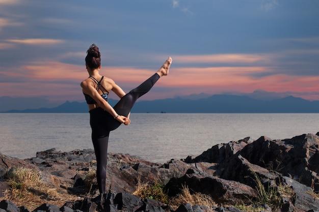Asiatin, die eine yogahaltung für balance und das ausdehnen tut.