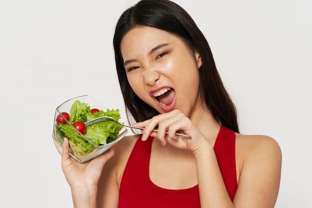 Asiatin, die einen salat isst