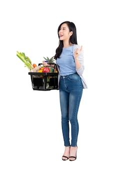 Asiatin, die einkaufskorb voll vom gemüse und von den lebensmittelgeschäften hält