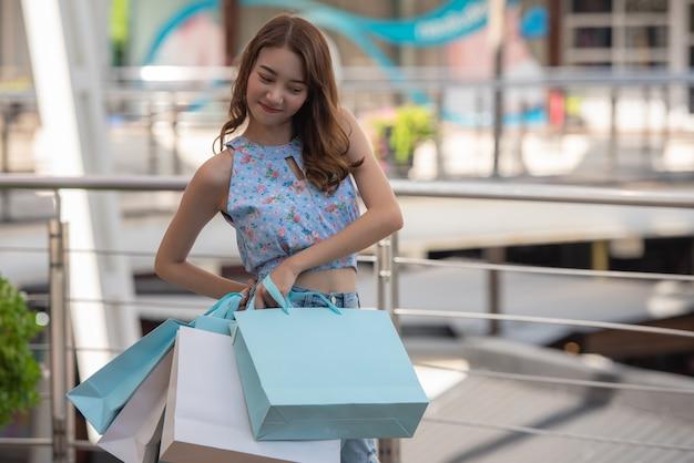 Asiatin, die einkaufstaschen am mall hält