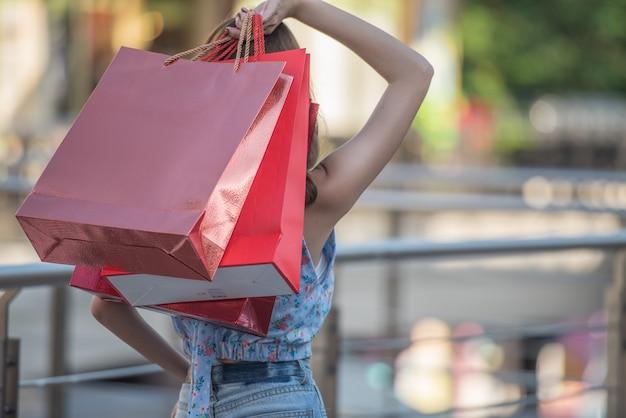 Asiatin, die einkaufstaschen und angehobene hände hochhält