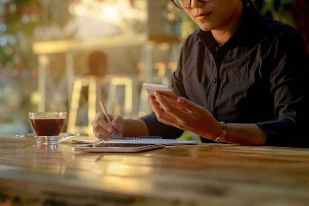 Asiatin, die entlang ihrer handys beim arbeiten anstarrt.