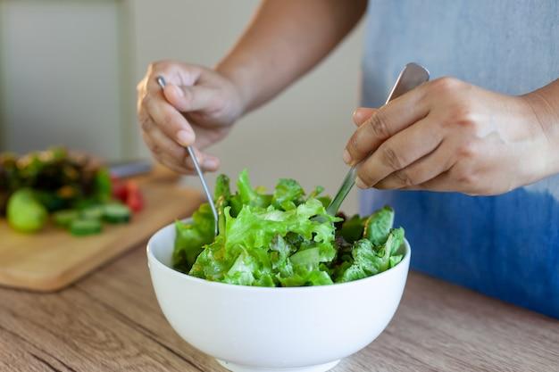 Asiatin, die frischgemüsesalatbestandteile in der küche mischt
