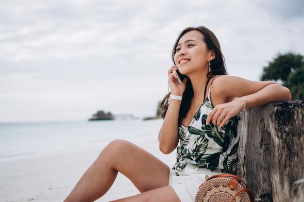 Asiatin, die g-telefon am strand auf ferien verwendet