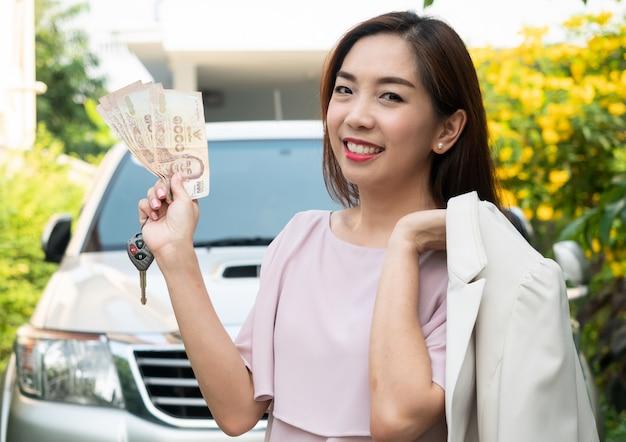Asiatin, die geld und autoschlüssel gegen ein auto hält. versicherung, darlehen und finanzen