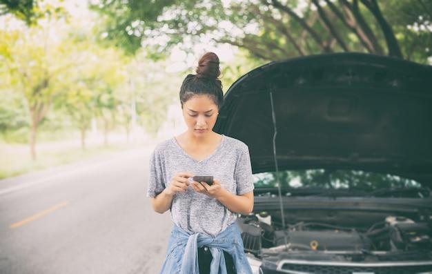 Asiatin, die handy beim schauen und betonten mann sitzt nach einem autozusammenbruch auf stree verwendet