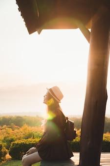Asiatin, die himmel mit sonnenuntergang- und blumenfeldern schaut