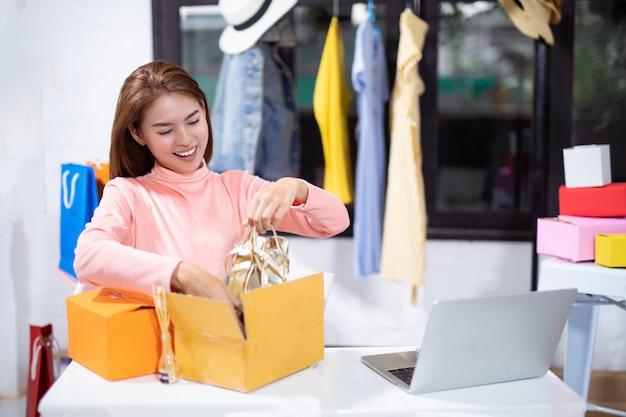 Asiatin, die ihr produkt beim sitzen im werkstatt-e-commerce-geschäftskonzept verpackt.