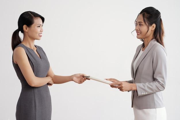 Asiatin, die ihrem weiblichen chef im anzug bei der arbeit dokumentenordner gibt