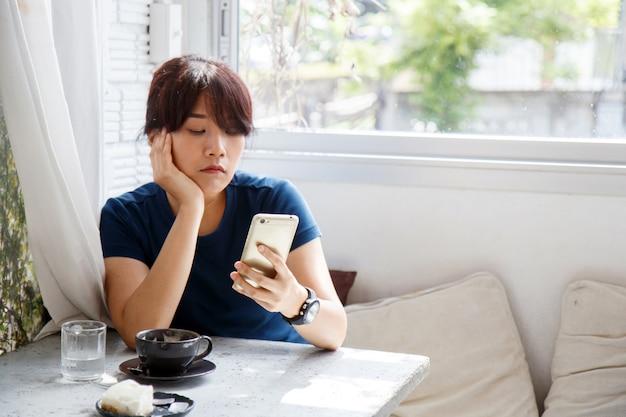 Asiatin, die im café und wartemitteilungsmitteilung auf ihrem smartphone sitzt