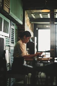 Asiatin, die im flippigen café sitzt und smartphone verwendet