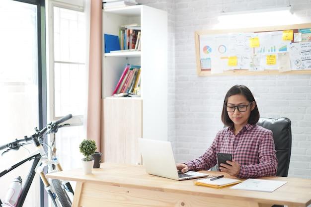 Asiatin, die im stilvollen halten smartphone mit dem arbeiten an laptop im innenministerium sitzt