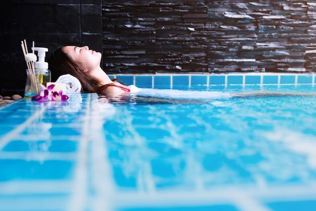 Asiatin, die im swimmingpool am kurort sich entspannt lockendes konzept.