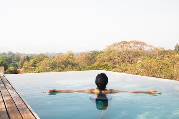 Asiatin, die im swimmingpool auf die dachoberseite schwimmt und sich entspannt