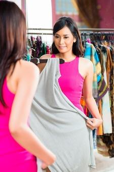 Asiatin, die in mode speicher kauft