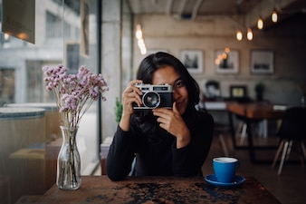Asiatin, die Kaffee im Kaffeestubekaffee mit Weinlesekamera trinkt