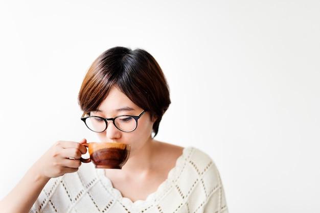 Asiatin, die kaffee mit hölzerner schale trinkt