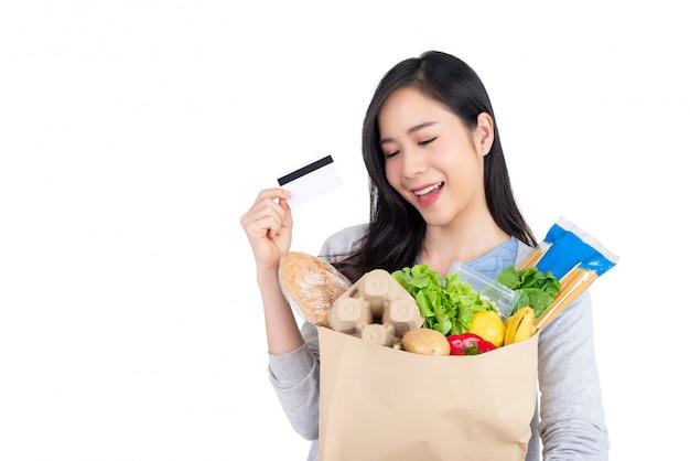 Asiatin, die kreditkarte für das gemüse- und lebensmitteleinkaufen verwendet