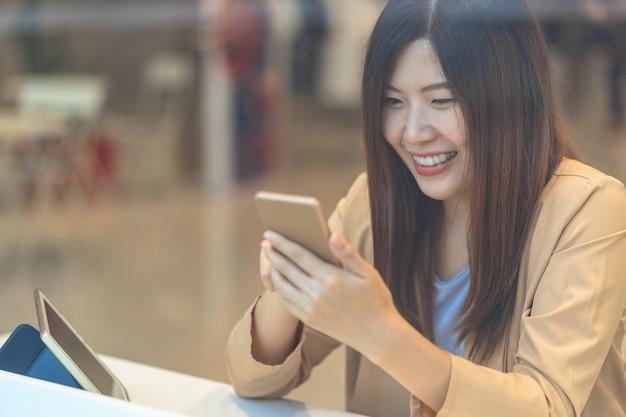Asiatin, die kreditkarte mit handy für das on-line-einkaufen im kaufhaus verwendet