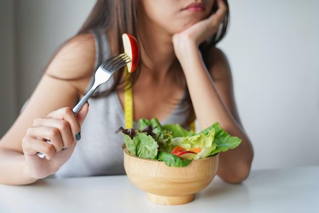 Asiatin, die langweilt, um salat- oder diätlebensmittel zu essen. diät-konzept
