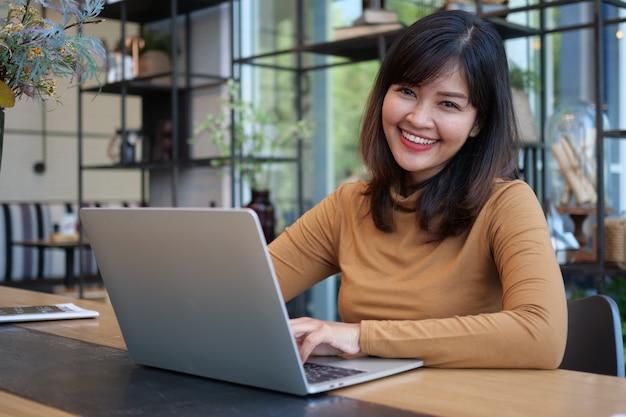 Asiatin, die laptop-computer im kaffeeshopcafé verwendet