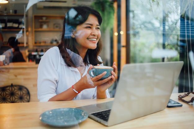 Asiatin, die laptop-computer im kaffeestubecafé verwendet