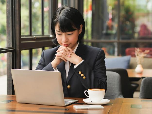 Asiatin, die laptop verwendet und kaffee im kaffeestube-café trinkt