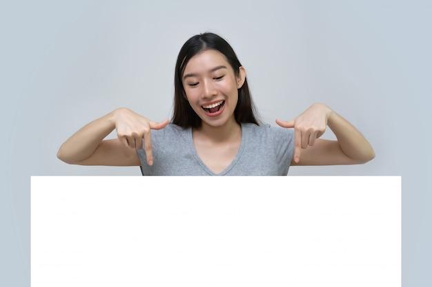 Asiatin, die leeres leeres anschlagtafelpapierzeichenbrett, werbungsfahnenzeichen hält