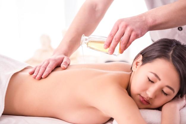 Asiatin, die massage mit badekurortöl im schönheitssalon hat.